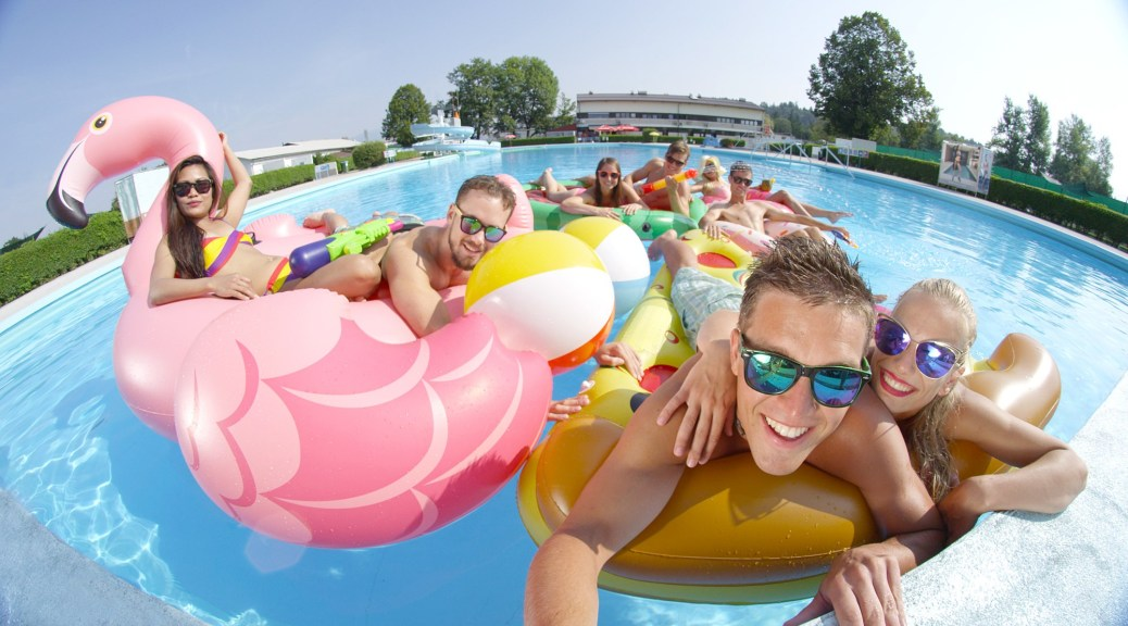 SELFIE CLOSE UP PORTRAIT: Happy smiling friends doing selfie while having water-gun fight on fun colorful floaties in pool. Young people on inflatable flamingo, pizza, watermelon and doughnut floats