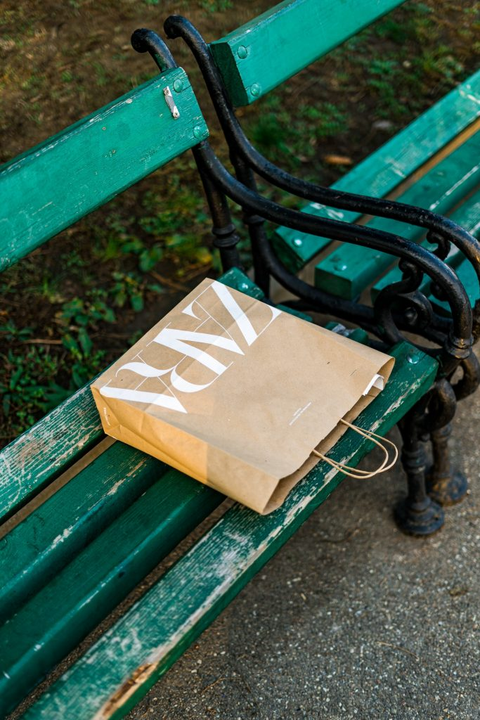 a paper bag from Zara on a bench