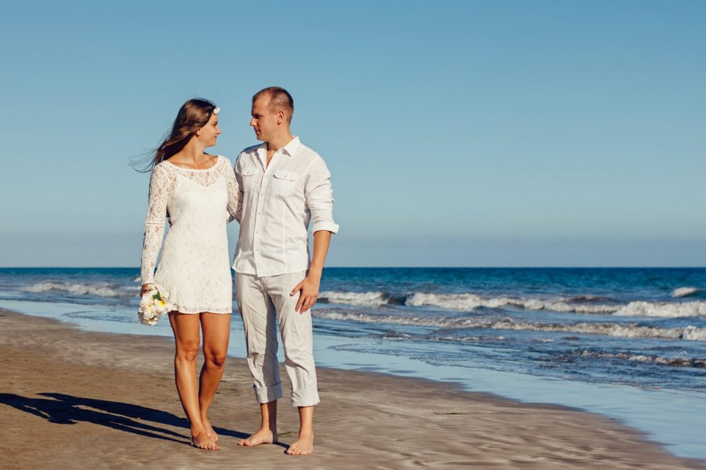bride and groom casually dressed for summer beach wedding