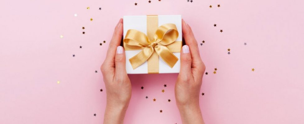 Womans hands holding gift or present box decorated confetti on pink pastel table top view. Birthday or wedding template or mockup.